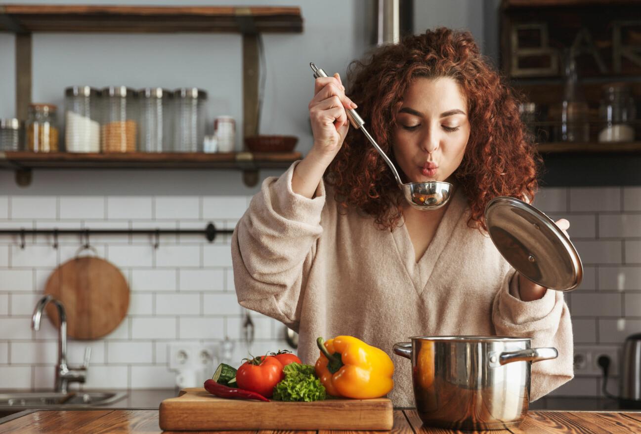 En rödhårig kvinna står i ett kök och provsmakar maten direkt ur soppsleven.