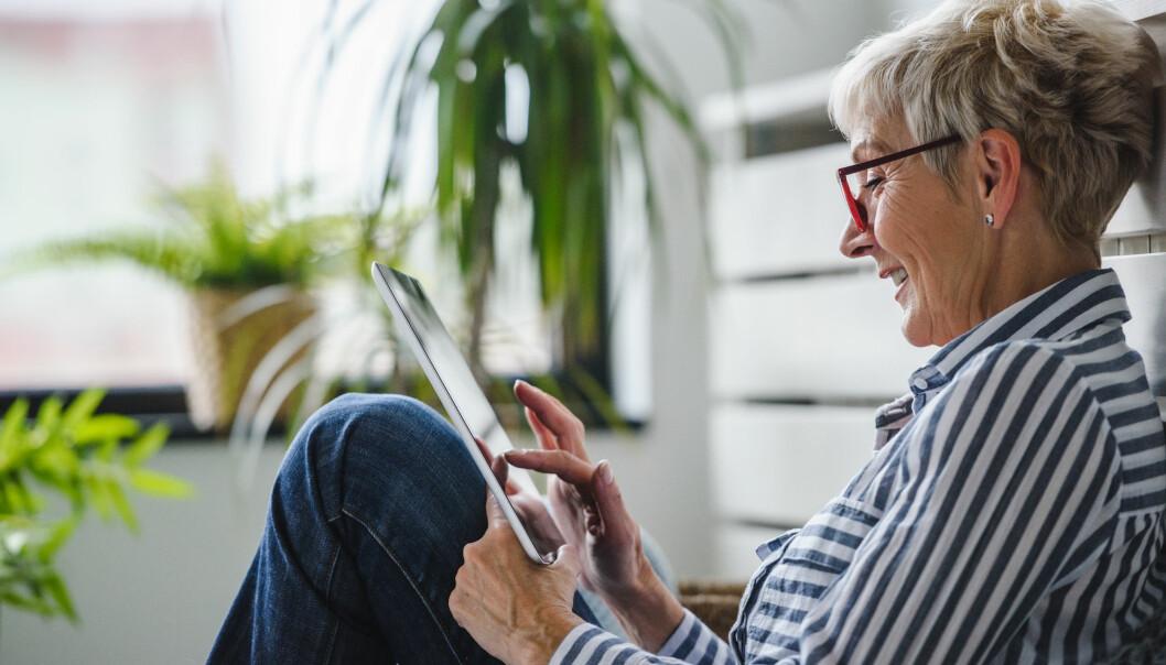Äldre kvinna löser korsord på läsplatta.