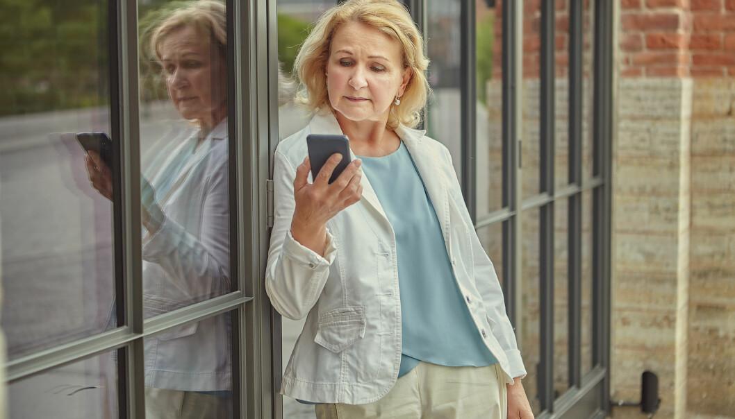 Ensam äldre kvinna med mobiltelefon.