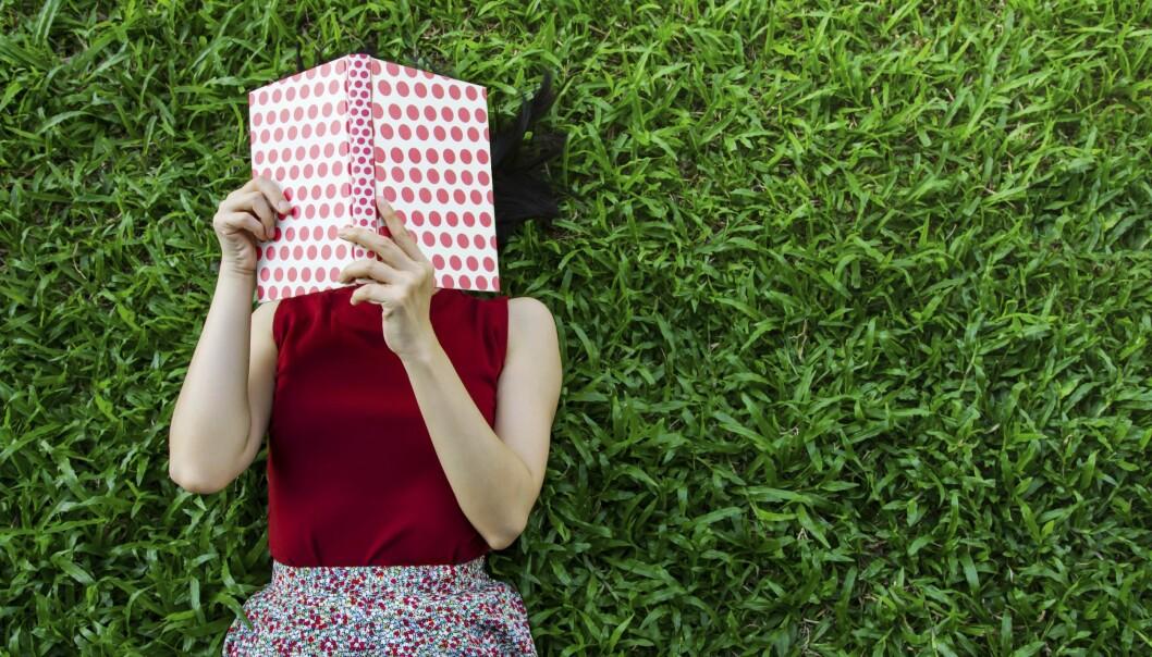 Kvinna läser en bok i gräset