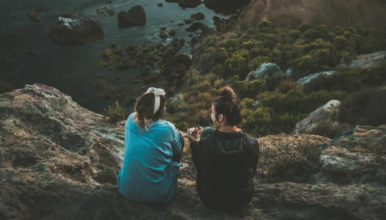 Väninnor som sitter på en klippa och pratar om hur de mår.
