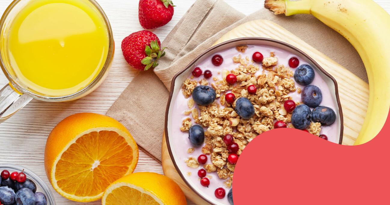 En skål med yoghurt, müsli och bär och ett glas apelsinjuice omringat av frukt och bär fotograferat uppifrån.