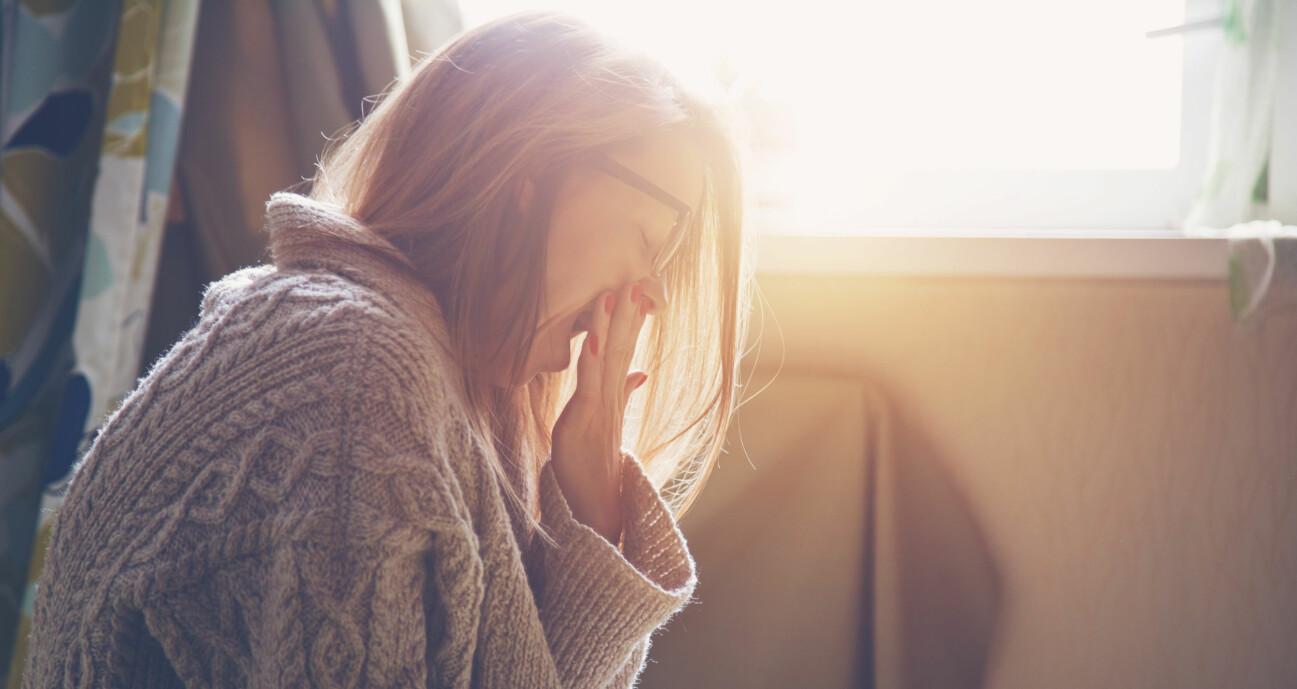 En kvinna som gäspar och är trött på grund av högt blodsocker.