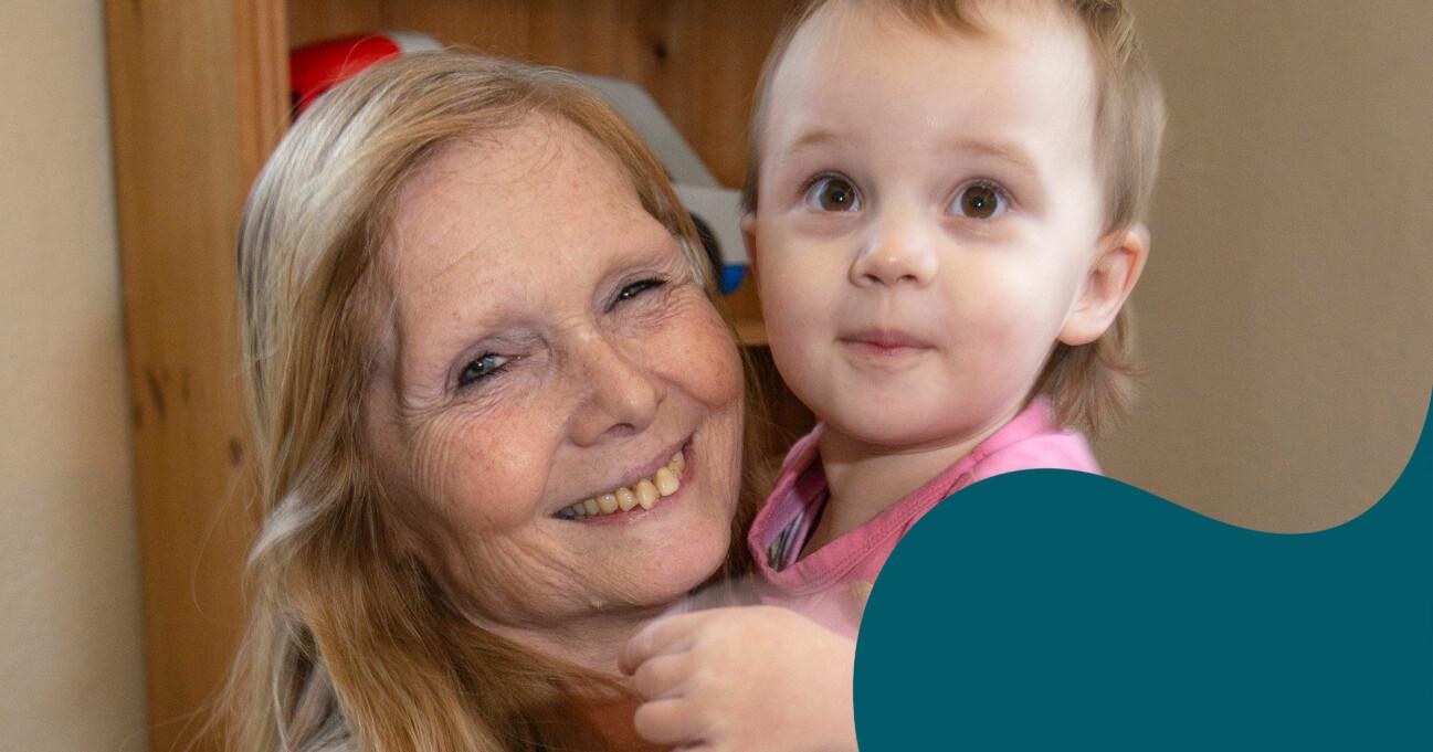 En leende Connie Kajhøj och barnbarnet Kida poserar framför kameran.