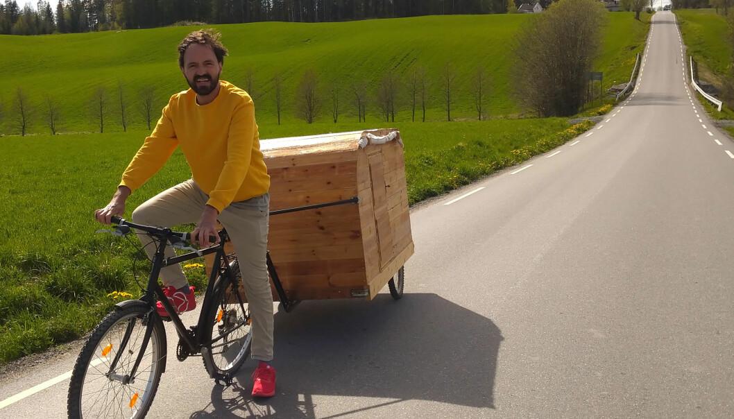 Mario Andrade cyklar med sin hemmabyggda cykelhusvagn.