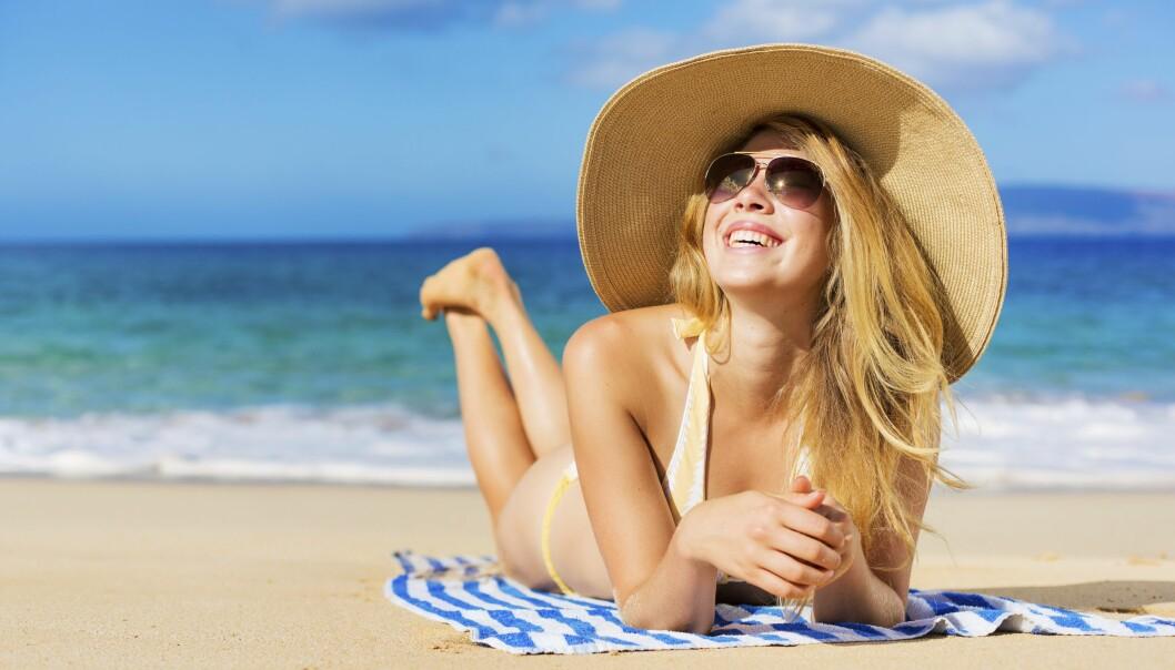 Kvinna med solhatt och solglasögon på stranden