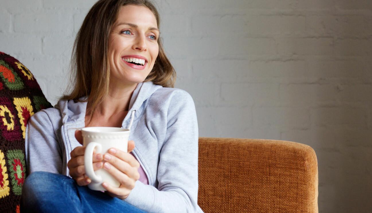 Glad kvinna dricker te i soffan.