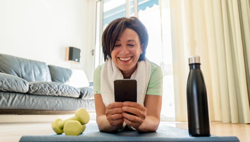 En kvinna ligger på sin yogamatta på hemmagymmet.