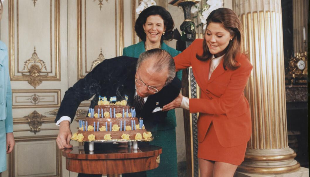Kungen blåser ut ljusen på sin tårta med Victorias hjälp på hans 50-årsdag.