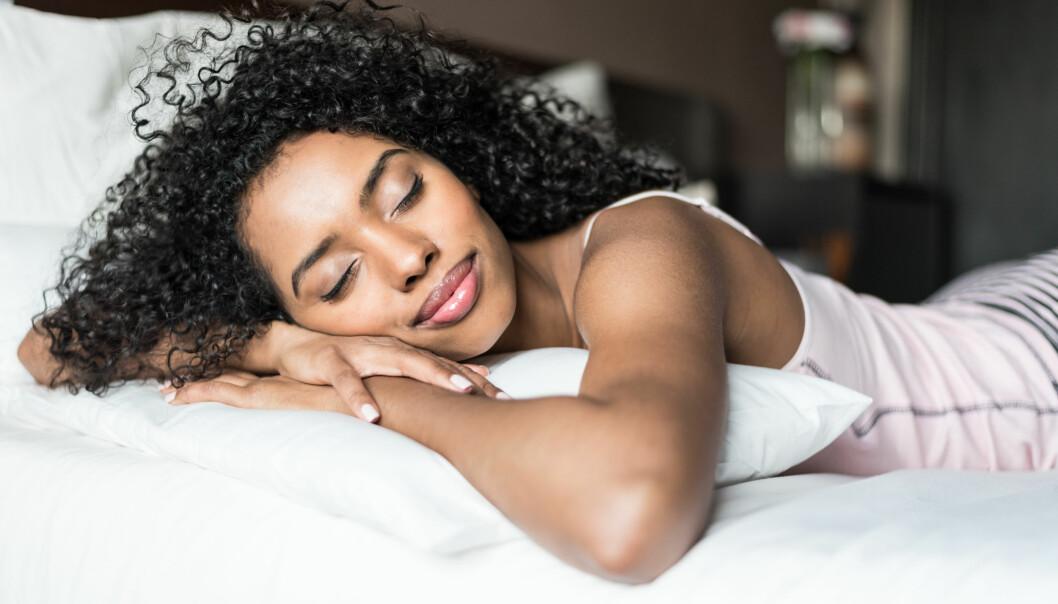 En kvinna ligger på en säng och sover med händerna under huvudet.