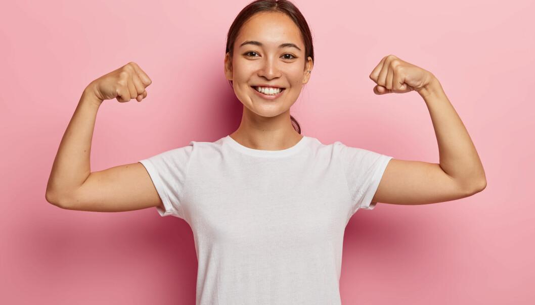 Glad kvinna visar sina armmuskler.