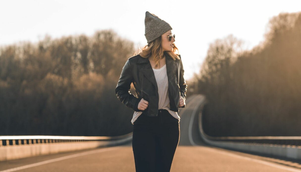 En kvinna med skinnjacka och mössa som står mitt på en väg.