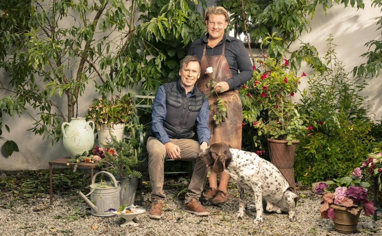 Karl Fredrik med en vit ros, sambon Petter och hunden i en grön och prunkande miljö.
