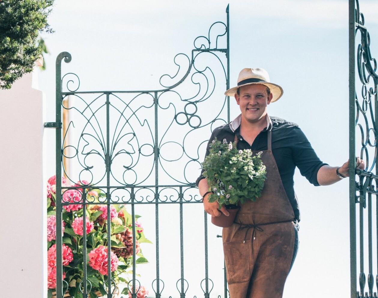 Glad Karl Fredrik vid järngrinden med en kryddväxt i famnen och stora hortensior på marken.