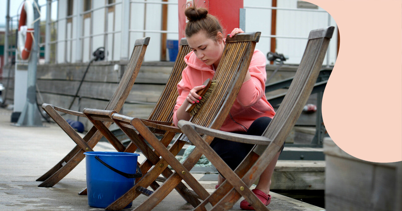 En kvinna rengör stolar i trä.