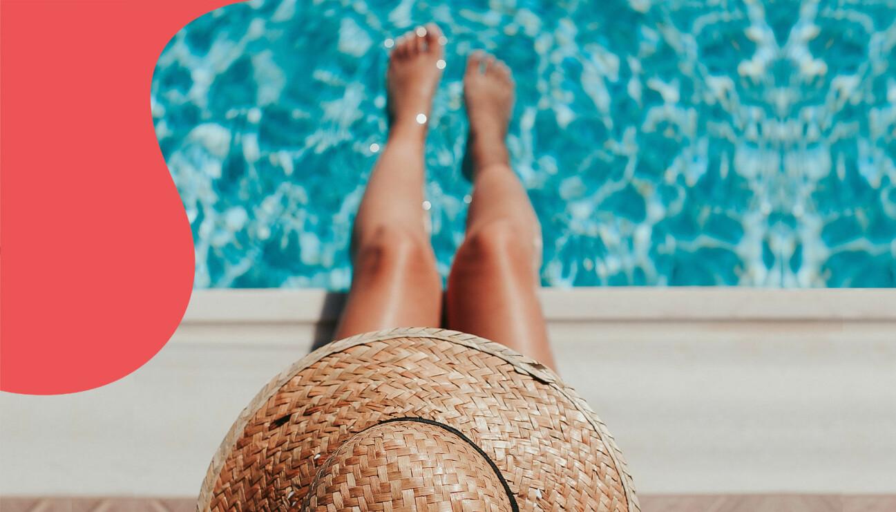 En kvinna i solhatt doppar fötterna i poolen.