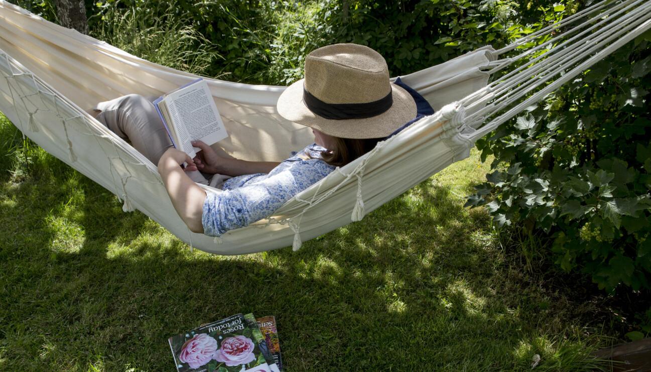 Kvinna i hängmatta som läser