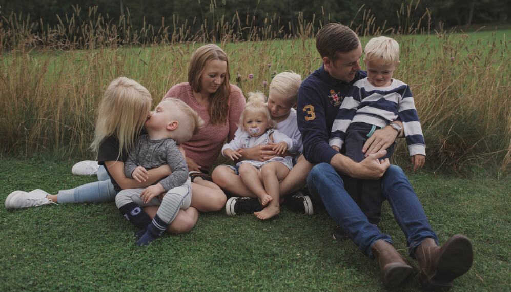 Malin och hennes make Calle sitter vid en äng med fem barn.