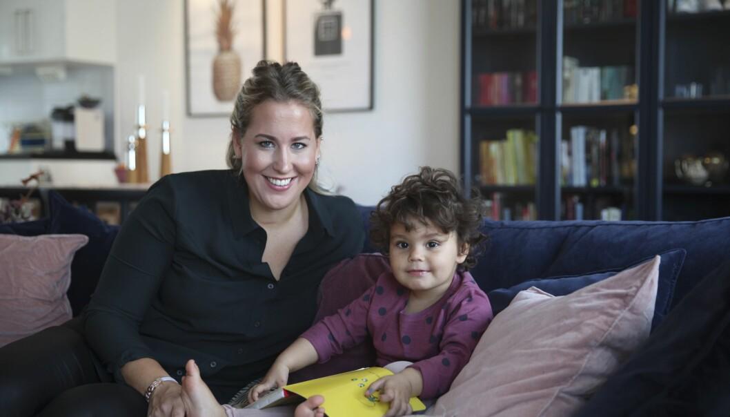 Lovisa sitter i en soffa och leker med dottern Lykke.