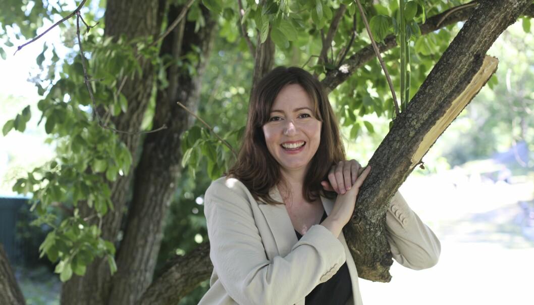 Skådespelaren Sanna Sundqvist står lutad mot ett träd.