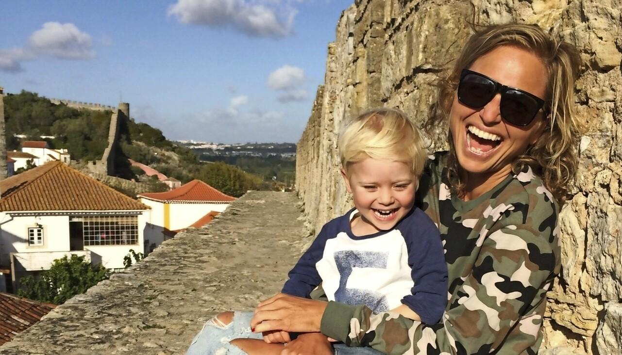 Johanna i solglasögon tillsammans med sin lille son i famnen.