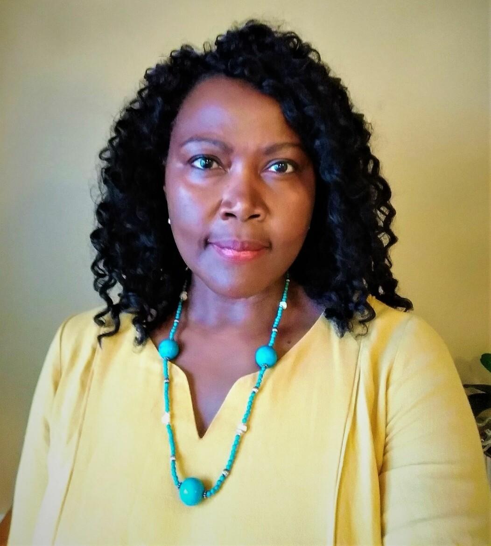 Irene Opira har gul tröja på sig och ser in kameran med ett subtilt leende på läpparna.