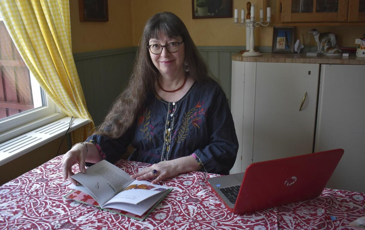 Irene Svensson bläddrar i sin färdiga bok, där hon sitter med sin laptop vid köksbordet.