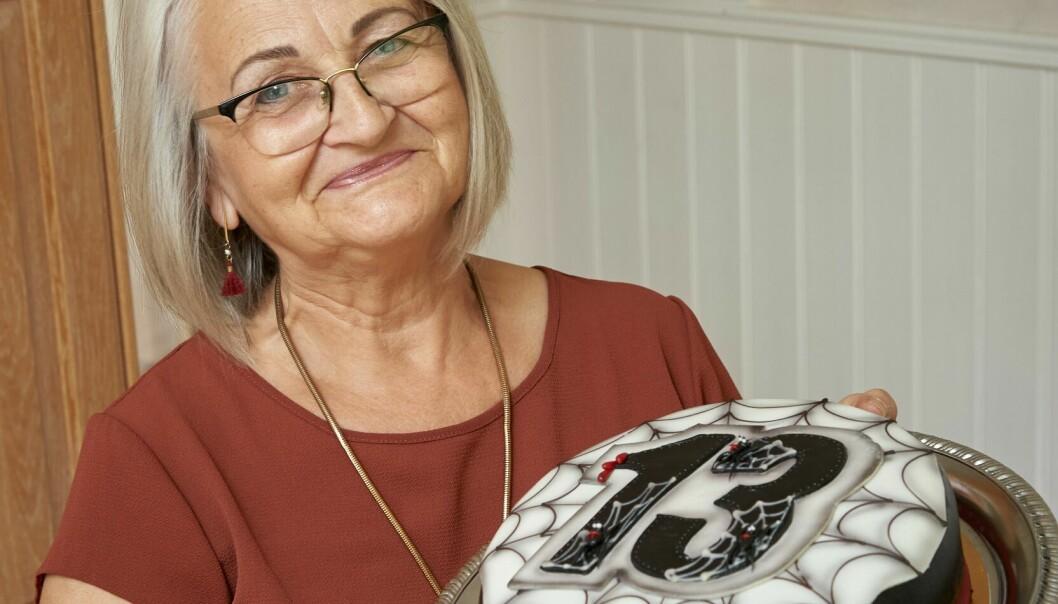 Jadwiga Persson håller en tårta med siffran 13, ler och berättar om hur 13 är hennes lyckonummer