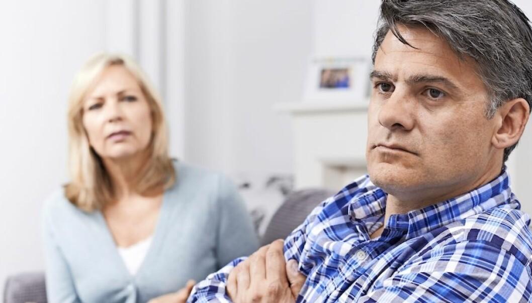 Arg man och orolig kvinna i soffa.