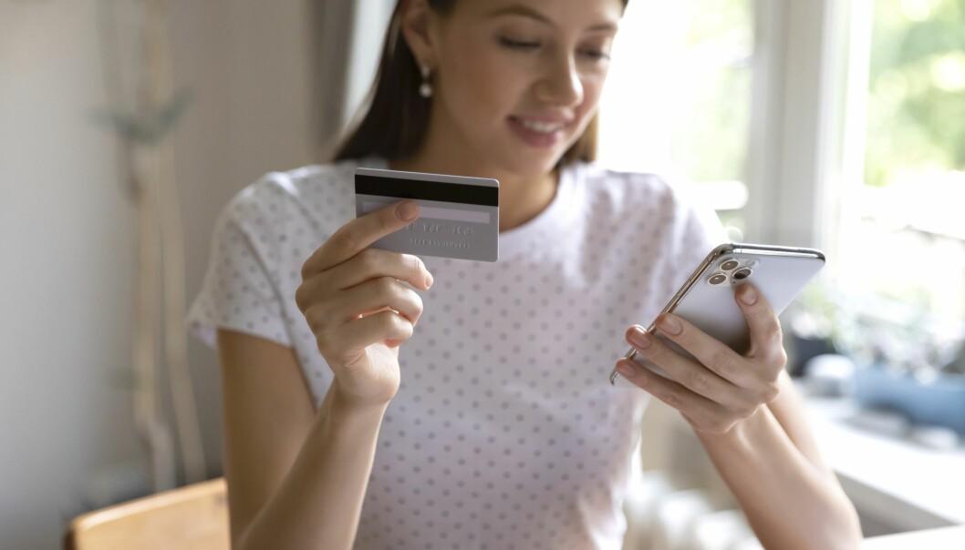 Ung kvinna sitter med ett bankkort och ska göra ett köp