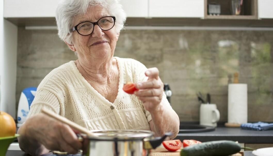 En äldre kvinna lagar mat i ett kök.