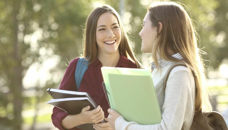 Två unga kvinnor pratar med varandra.
