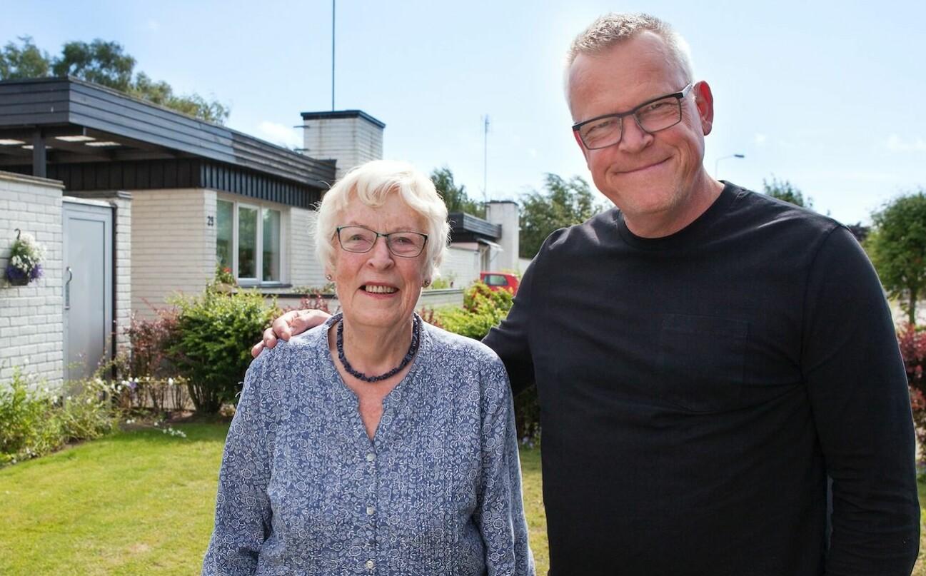 Janne Andersson håller om sin mamma Gunni Andersson i trädgården utanför vitteglade barndomshemmet.