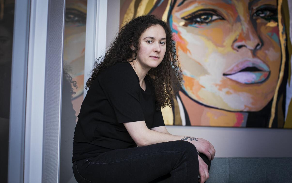 Jasmina sitter på soffkanten i Talitas kontor i Enskede, framför en tavla som föreställer en kvinna.