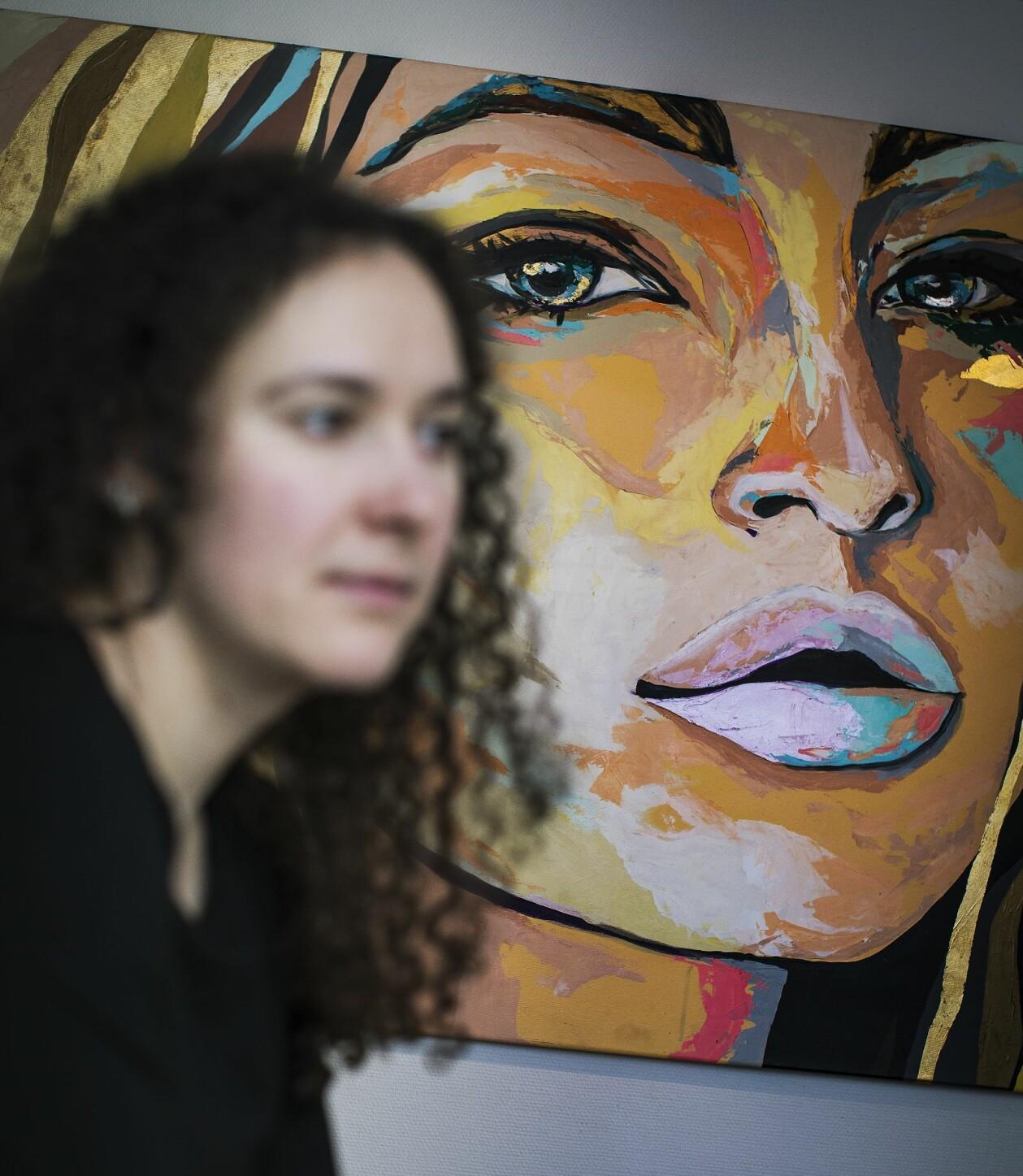 """""""Jasmina"""" som är suddig i framgrunden sitter framför en tavla på Talitas kontor i Stockholm."""