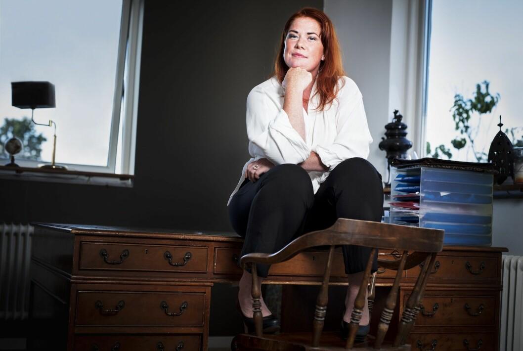 Jenny Küttim sitter på ett skrivbord med hakan i handen och tittar in i kameran