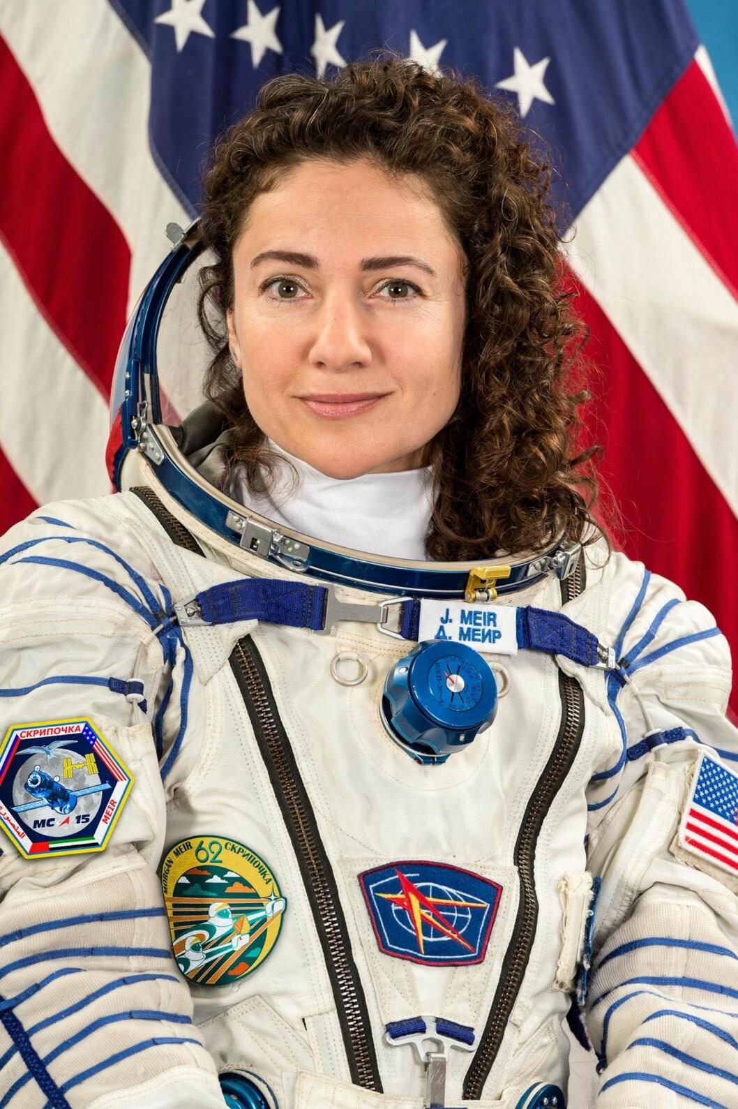 Astronauten Jessica Meir med den amerikanska flaggan i bakgrunden.