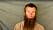 Johan Gustafssonstår mot ett skynke och har långt skägg efter en tids kidnappning i Mali