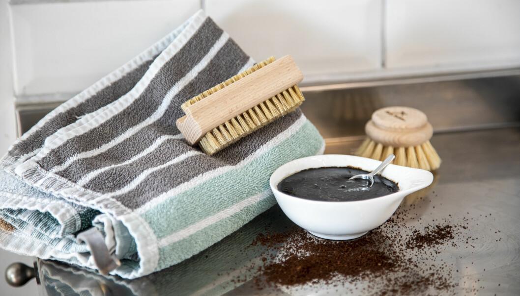 Kaffeskrubb med en handduk och nagelborste bakom. Kaffepulver ligger på diskbänken.