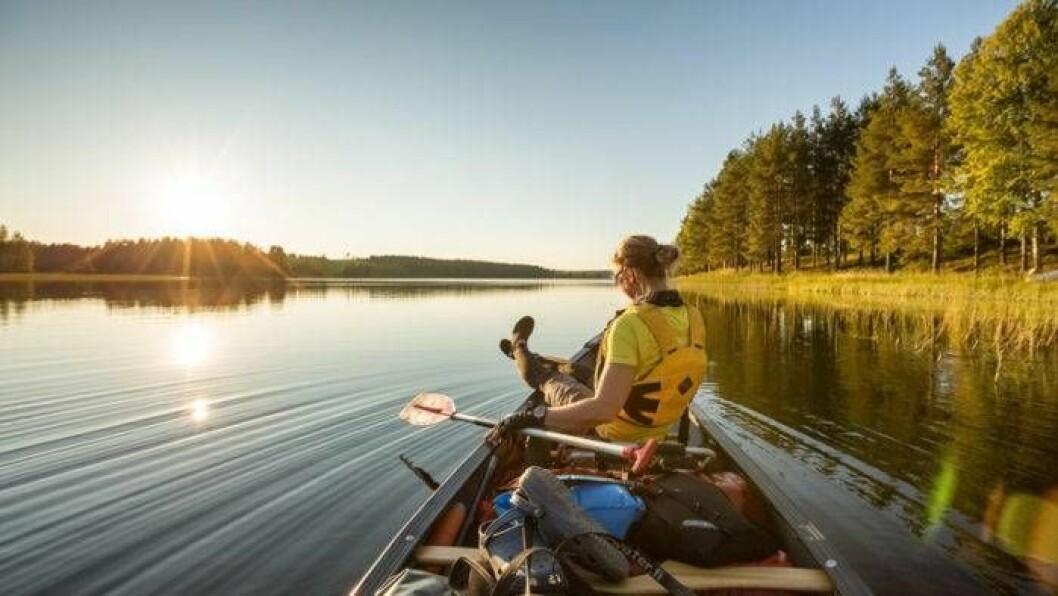Kvinna som är ute med båten vid en sjö