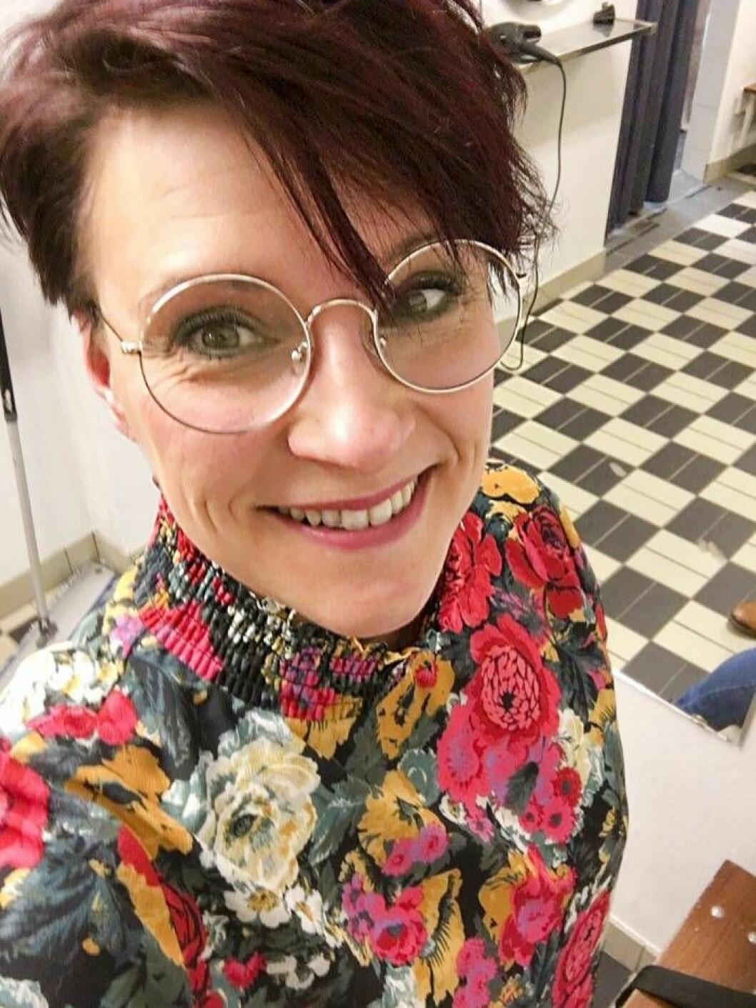 Selfie av glad och pigg kvinna med stormönstrad topp, runda glasögon och kort mörkt hår.
