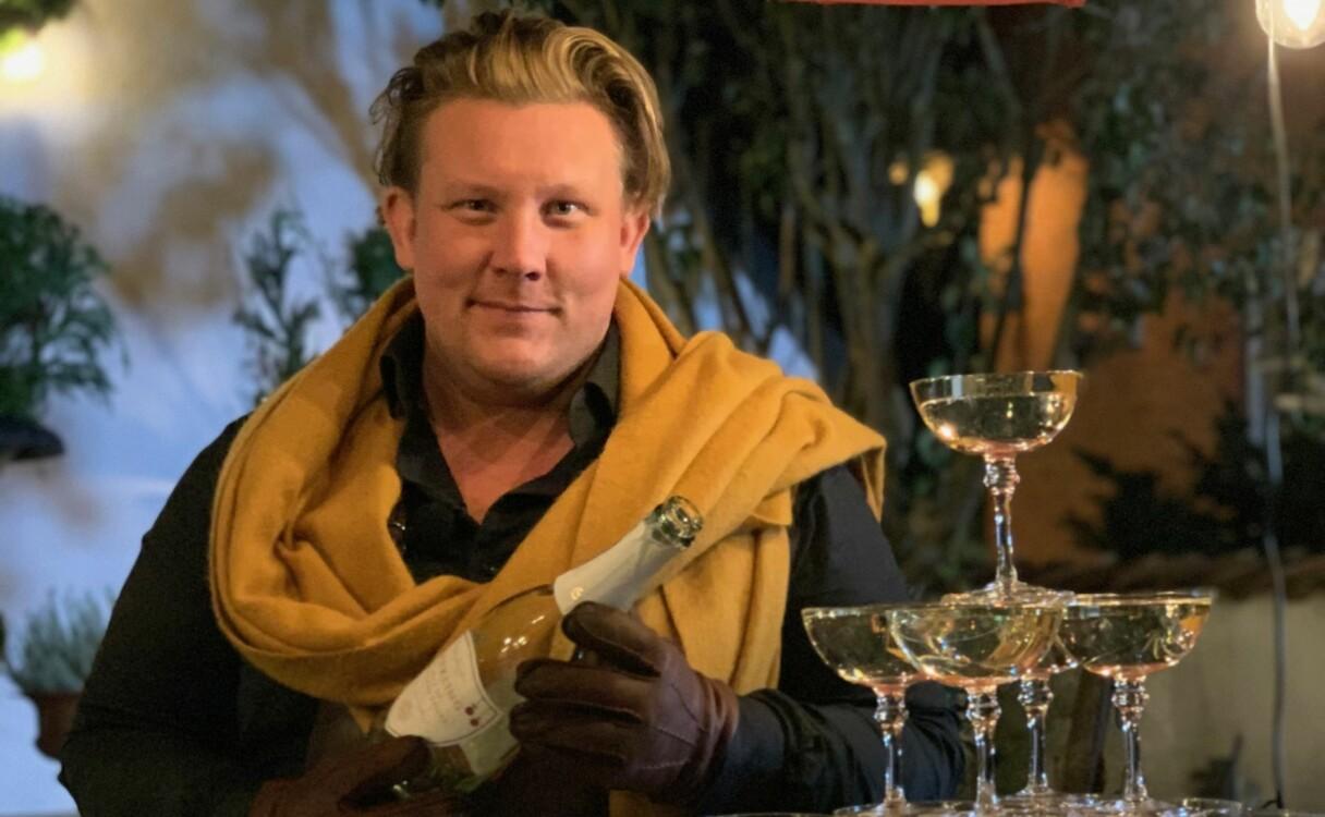 Karl Fredrik Gustafsson häller upp champagne i glas ställda i pyramid.