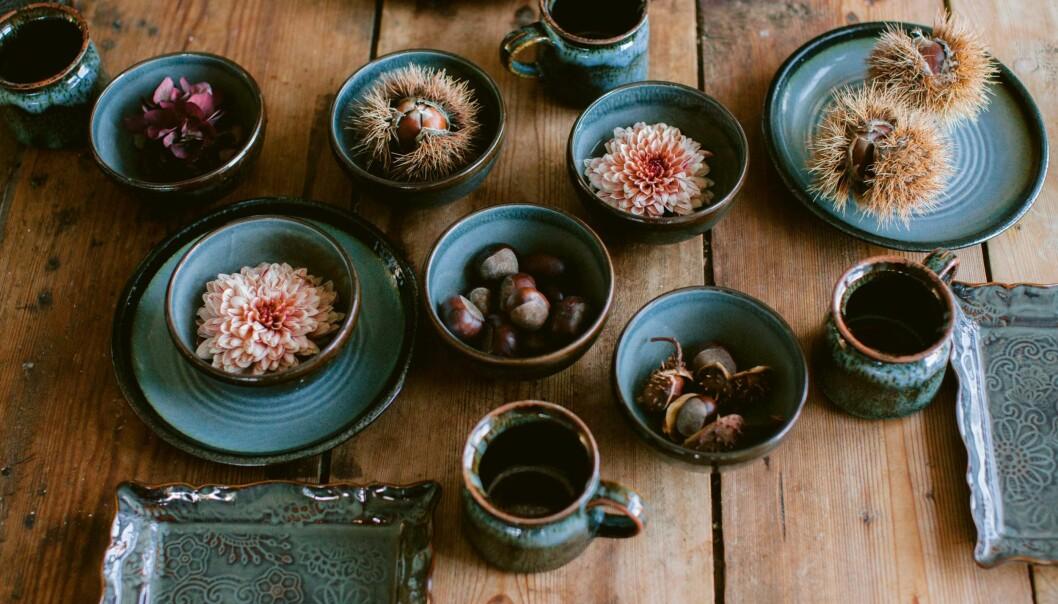 Kastanjer, krysantemum och hortensia i skålar på bordet.