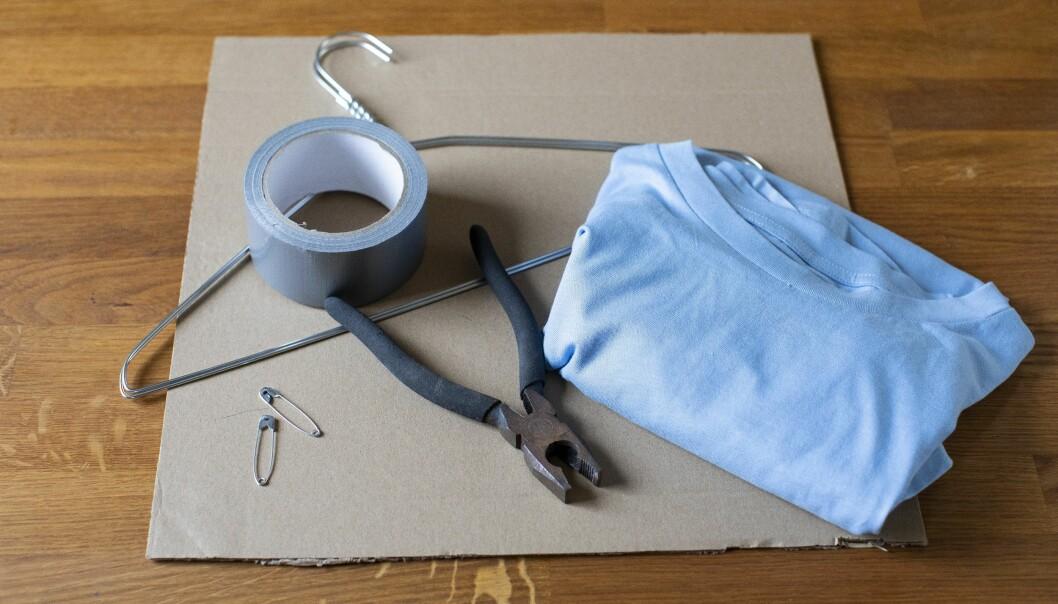 Kattältet gör du med en återbrukad t-shirt, två stålgalgar, lite papp och säkerhetsnålar.