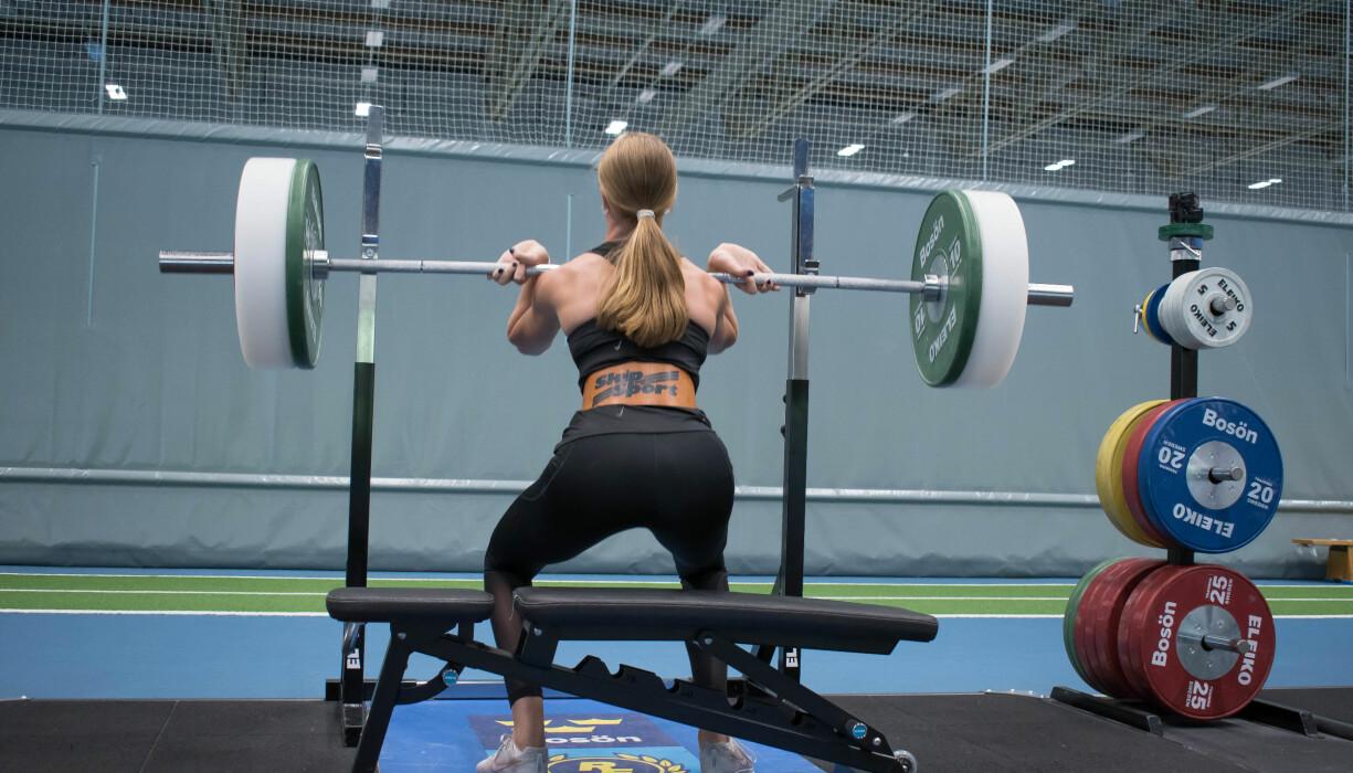 Kvinna har lyft upp en skivstång på axlarna och gör knäböj för att träna upp sin styrka.