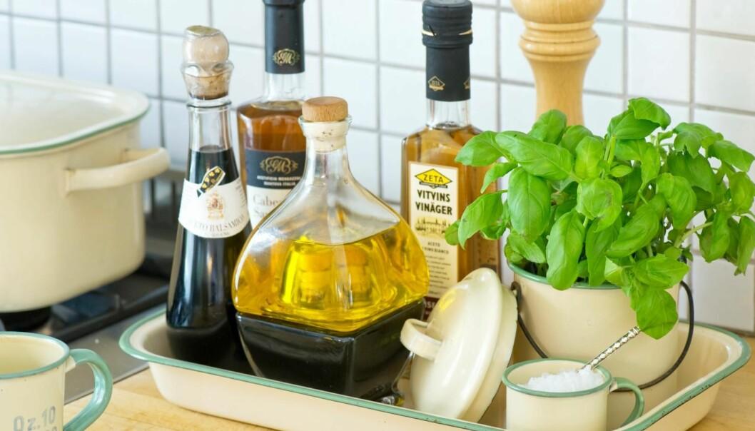 Flaskor med olja och vinäger står på ett emaljfat från Kockums tillsammans med en kruka basilika i en hink i emalj från Kockums. Bakom syns vitt kakel.