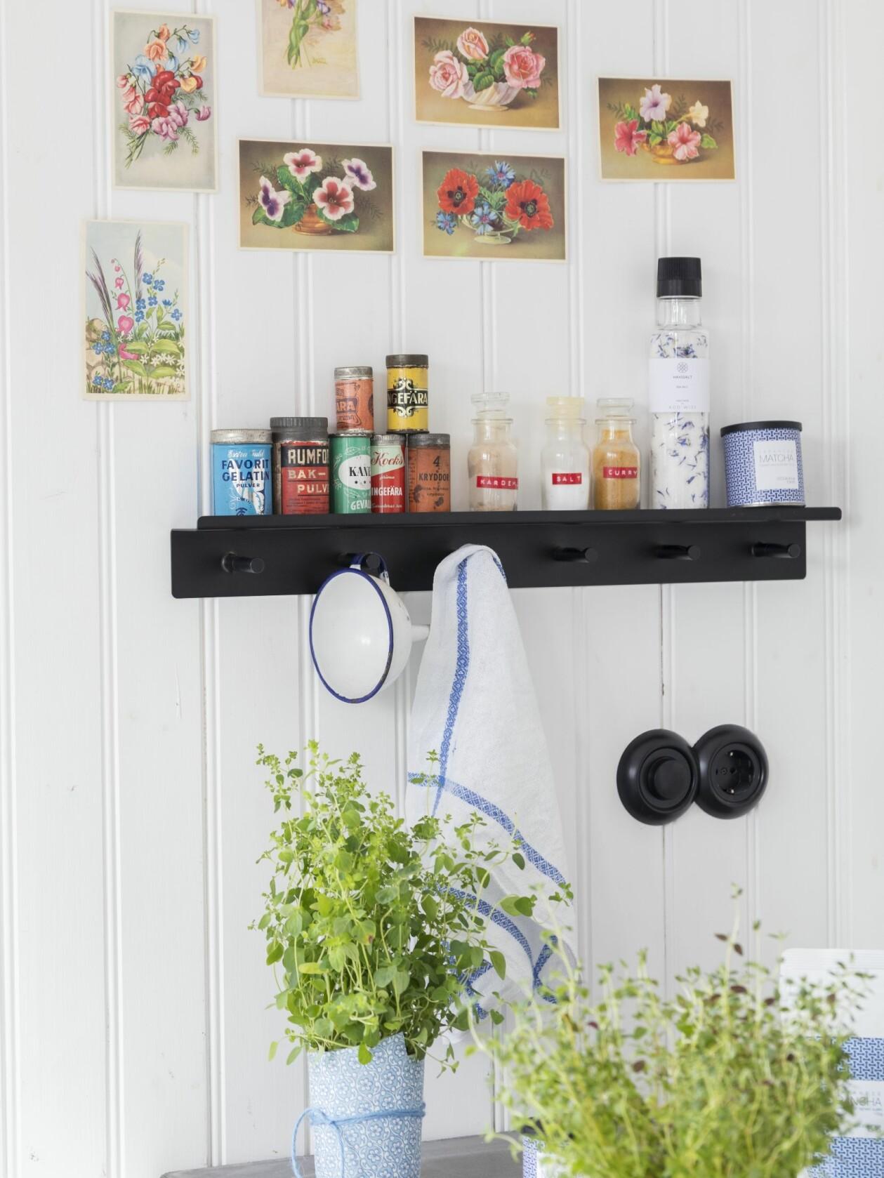 Köksvägg med vykort och kryddhylla