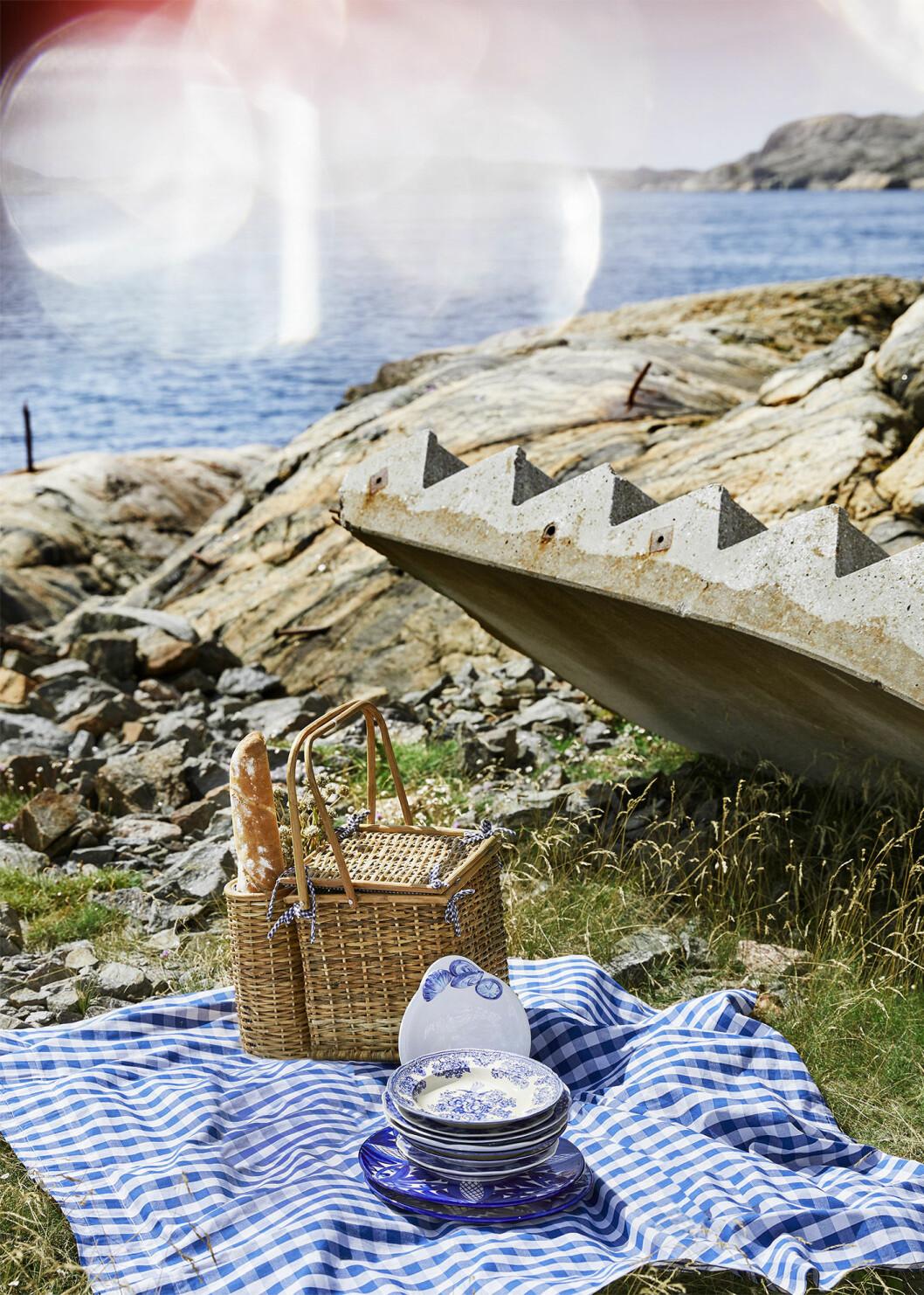 I gräset ligger en blåvit rutig filt med en korg och blåvita tallrikar på. I bakgrunden syns hav och klippor.