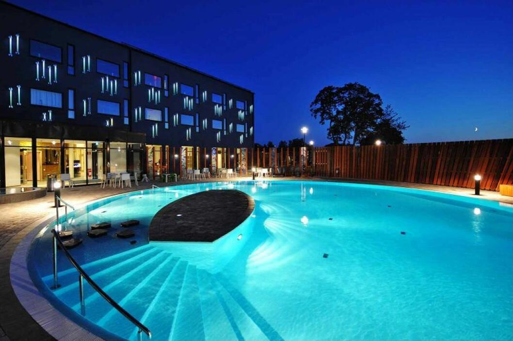 En pool utomhus som är upplyst i natten