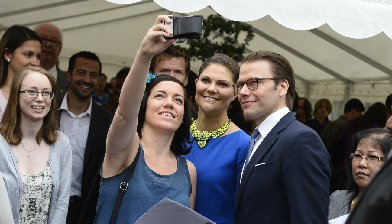 Kronprinsessan Victoria och Prins Daniel poserar för en selfie med ett gäng från allmänheten.